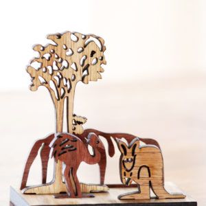 A wooden mini landscape of an Australian image with Uluru, a kangaroo, an emu and a koala in a gum tree. Four wooden images sit into a wooden base to make up the 3D landscape.