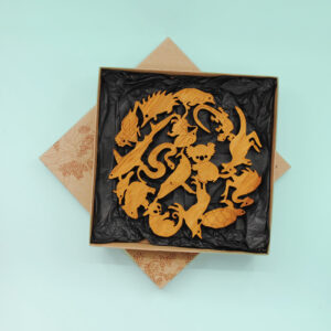 A round wooden Australian animal design trivet in a recycled card presentation box