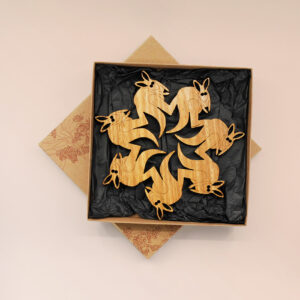 A round wooden kangaroo design trivet in a recycled card presentation box
