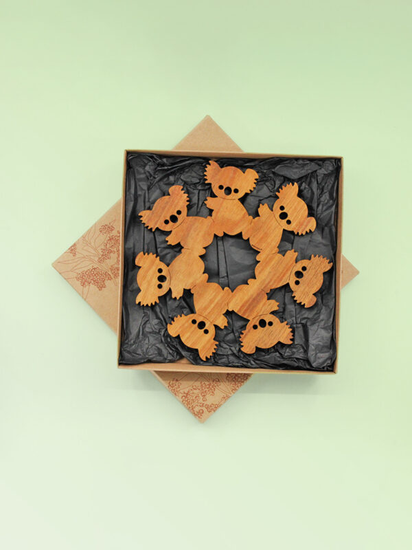 A round wooden koala design trivet in a recycled card presentation box