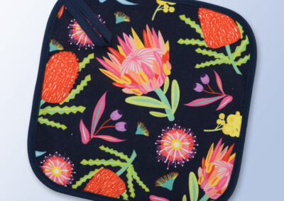 Insulated pot holder with an Aussie Flora pattern on the fabric and a dark navy edging with a hang tab.
