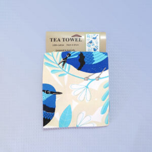 A sandy coloured cotton tea towel with Blue Wren images printed on it.