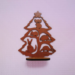 A wooden Australian made Christmas tree. It is a cut out of a tree with a koala, a wombat, an echidna, a kangaroo and a platypus in it and it stands on a little wooden stand.