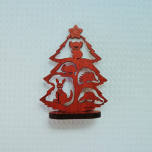 A small wooden Australian made Christmas tree. It is a cut out of a tree with a koala, a wombat, an echidna, a kangaroo and a platypus in it and it stands on a little wooden stand.