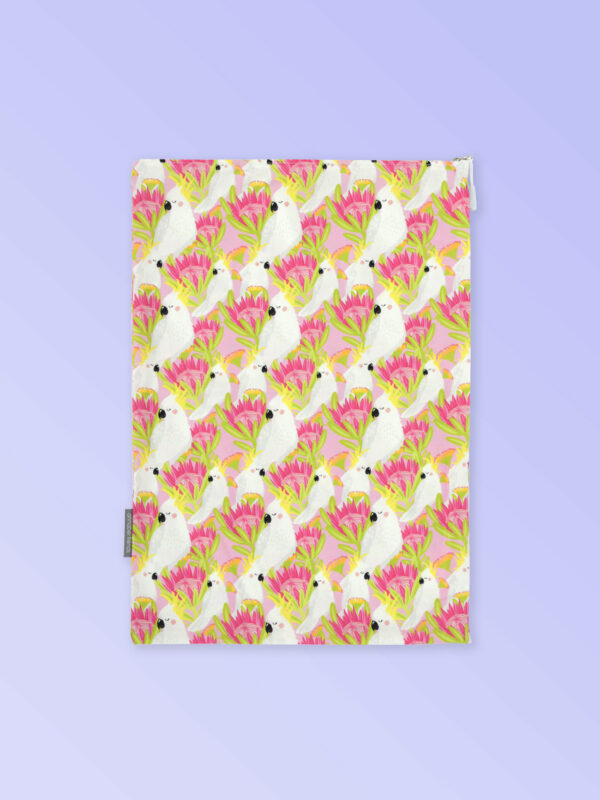 A fabric travel laundry bag with a pink cockatoo pattern on it and a zip closure.