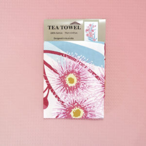 A white cotton tea towel with a large pink flowering gum print on it.