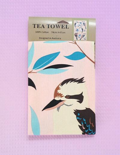 A light pink cotton tea towel with Kookaburra images printed on it.