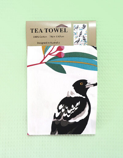 A cream cotton tea towel with Magpie images printed on it.