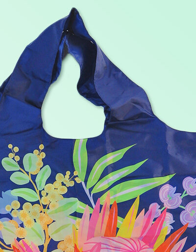 A close up of a foldable strong shopping bag printed with illustrations of Australian flora. It has a navy background. Made with polyester.