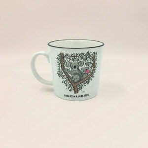 A porcelain mug with a whimsical illustration of a koala in a gum tree on it.