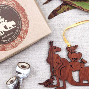 A wooden decoration featuring Australian animals. It is next to its recycled cardboard box.