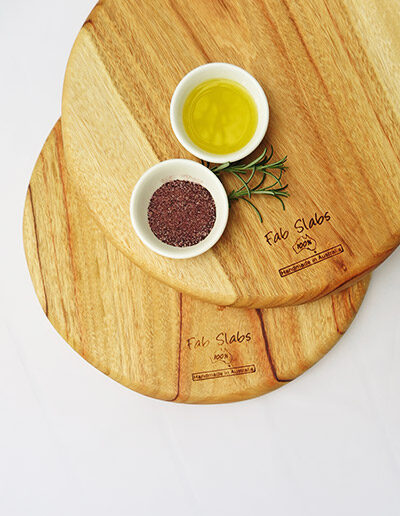 Two wooden pizza chopping boards with a dish of salt & a dish of oil