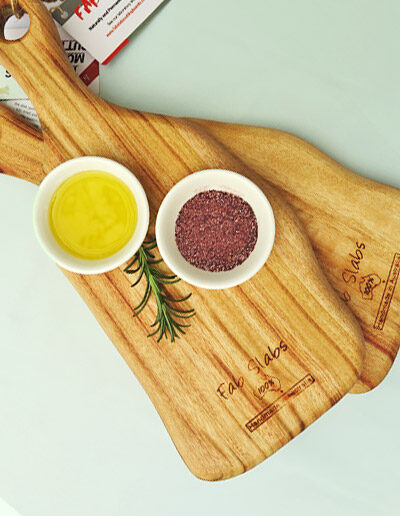 Two small wooden paddle chopping boards with a dish of salt & a dish of oil