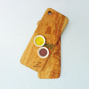 Two small wooden chopping boards with a dish of olive oil and a dish of salt